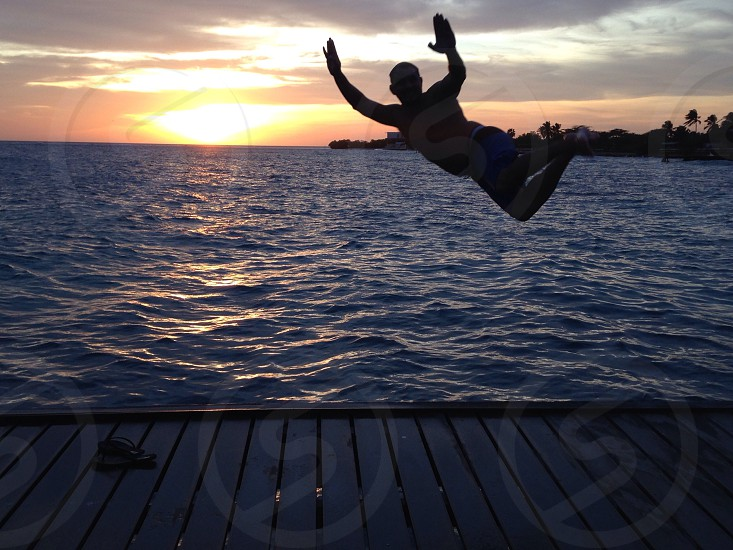 Dad jumping in sunset Aruba Caribbean island  photo