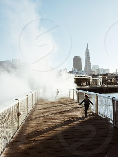boy running on dock over sea during daytime photo