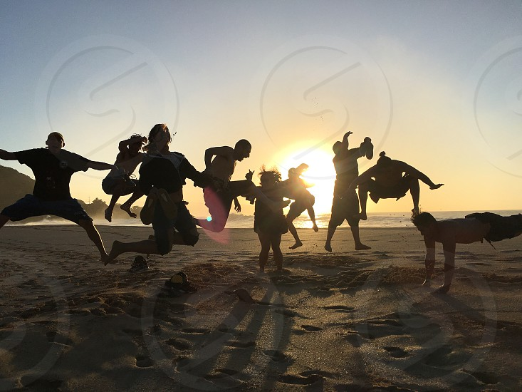 silhouette of people jumping on shore photo