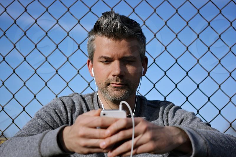 man wearing grey long sleeve shirt using smartphone and earphones photo