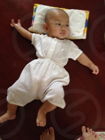 baby boy wearing white shirt and shorts lying on red spread floor photo