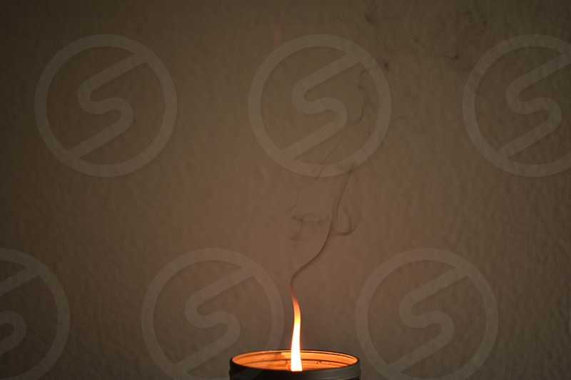 lighted candle and grey container behind beige concrete wall photo
