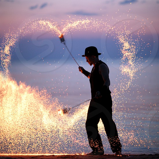 Fire magician making different shapes with fire on sea shore. photo