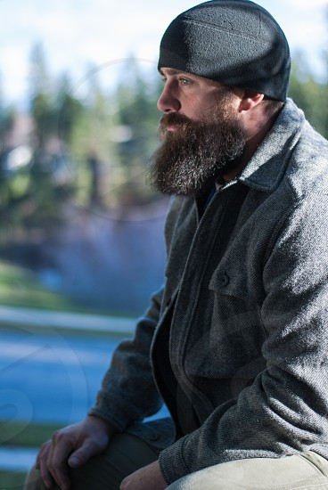Bearded man sitting outdoors with hands on knees and looking away from camera photo