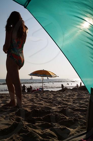Beach seashore relaxing beach sand Pacific Ocean bathing suit beach umbrella tent young woman sun shade summertime  photo