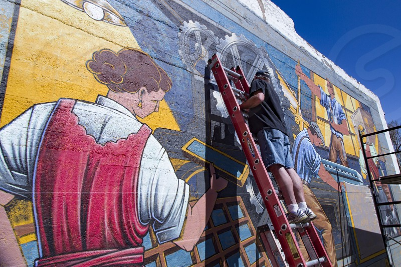 Artist working on mural in Mancos Colorado photo