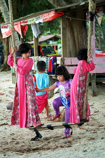 girl in purple frozen outfit stepping on a swing where 2 girls in pink dress is standing photo