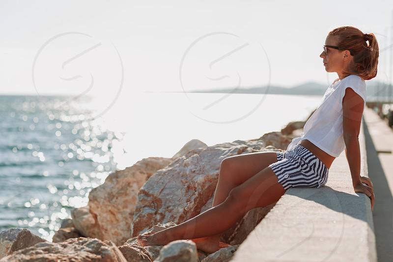 Young woman enjoying sunset in a marina photo