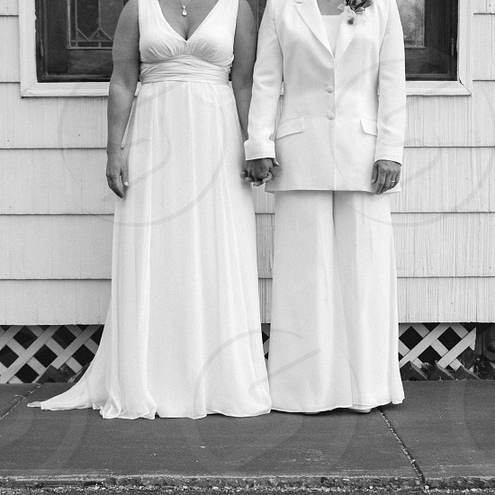 Same sex couple holding hands on their wedding day. photo