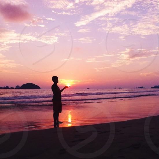man on seashore with sunset photo