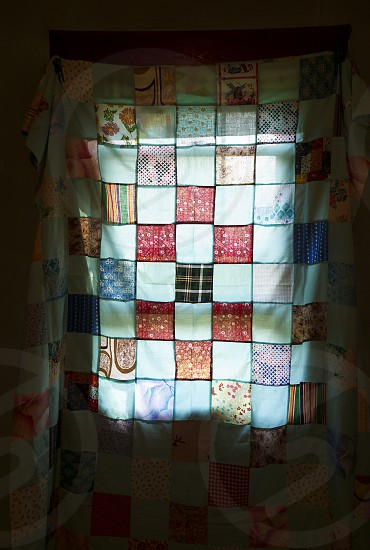 Textile - Quilt Hanging Over a Window photo