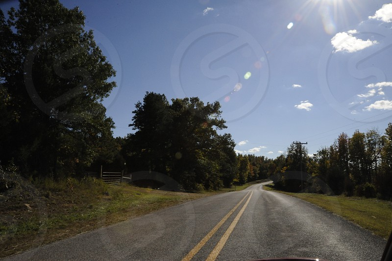 Two lane highway in forested area with blue sky and lens flare. photo