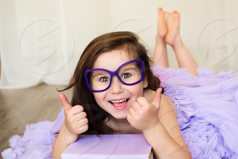 Happy cute little girl in purple glasses bold home sweet funny emotions  photo