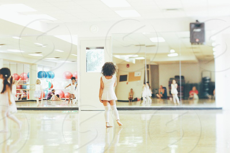 girl in white ballet dress standing in front of mirror photo
