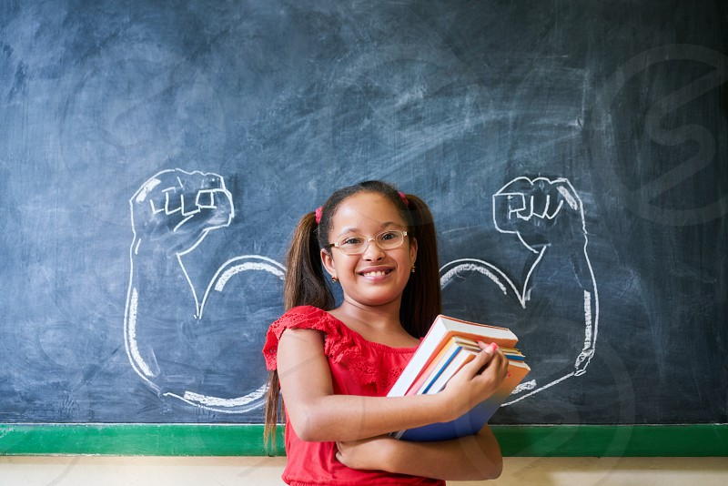 Concept on blackboard at school. Intelligent and successful hispanic girl in class. Portrait of female child smiling looking at camera holding books against drawing of muscles on blackboard               photo