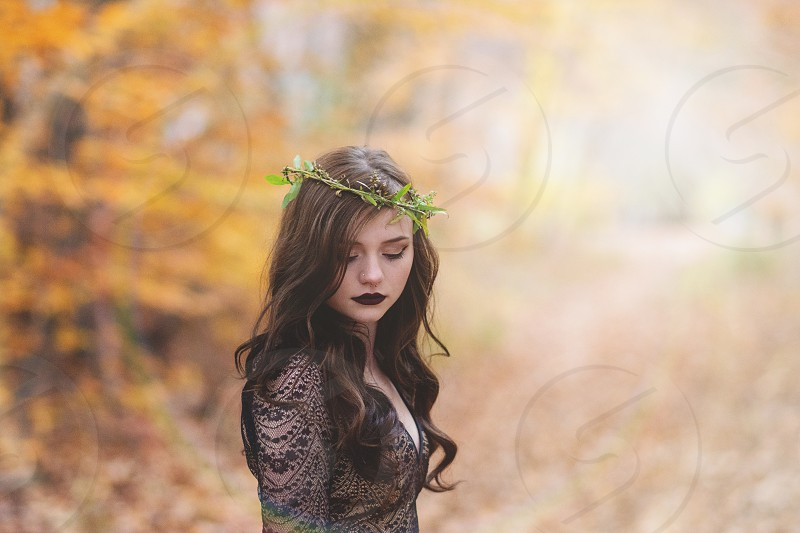 woman in black lace dress in fall forest with floral crown photo