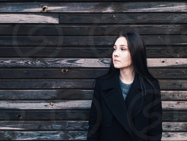 woman with black long hair in black jacket standing near brown wooden wall during daytime photo