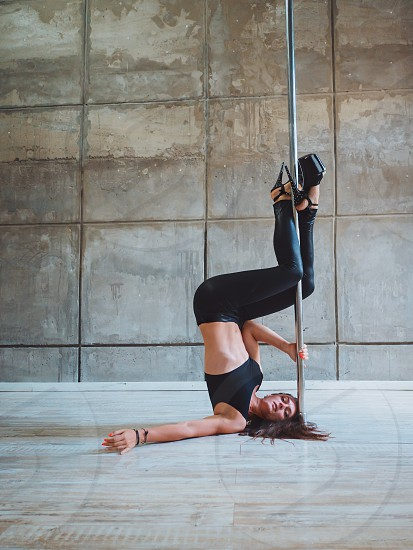 Young sexy slim woman pole dancing in grey interior.BeautifulAttractive girl performing pole dance. Shot with industrial concrete background.Lady with good figure dancing on pylon photo