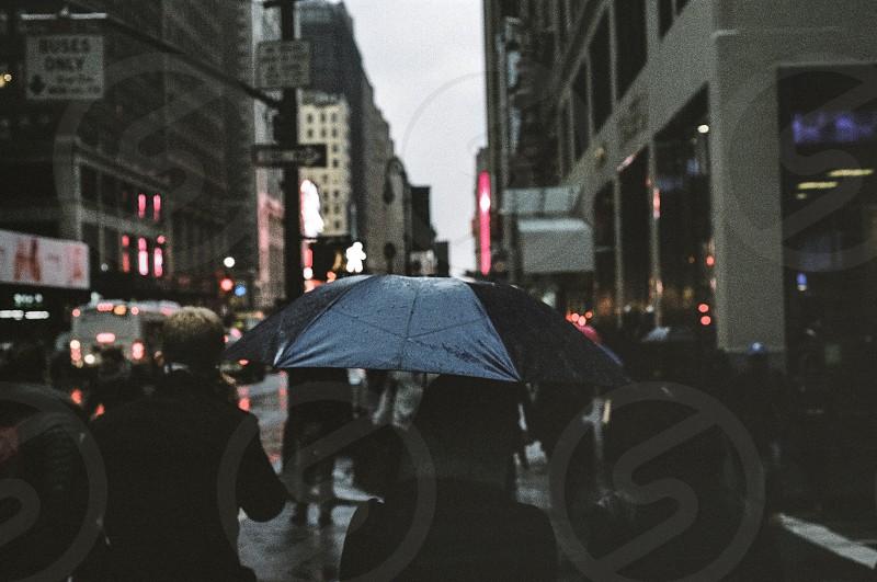 women using black umbrella walking near highway under high rise building on rainy day during daytime photo
