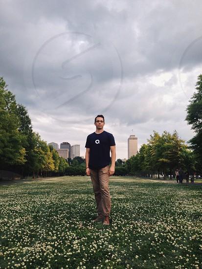 man in white heart printed black round neck t-shirt standing photo