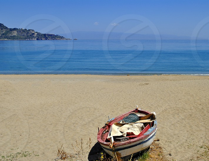 empty sandy beach with abandoned boat photo