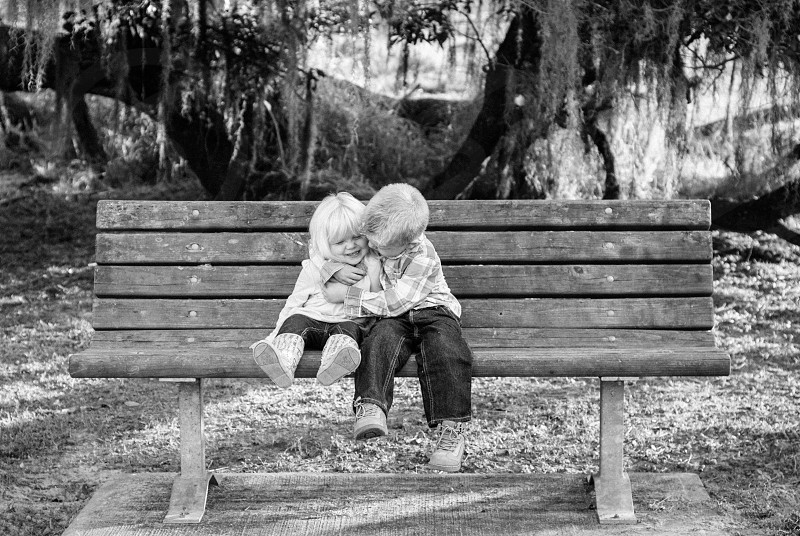 Brother and sister share a kiss on a park bench. photo