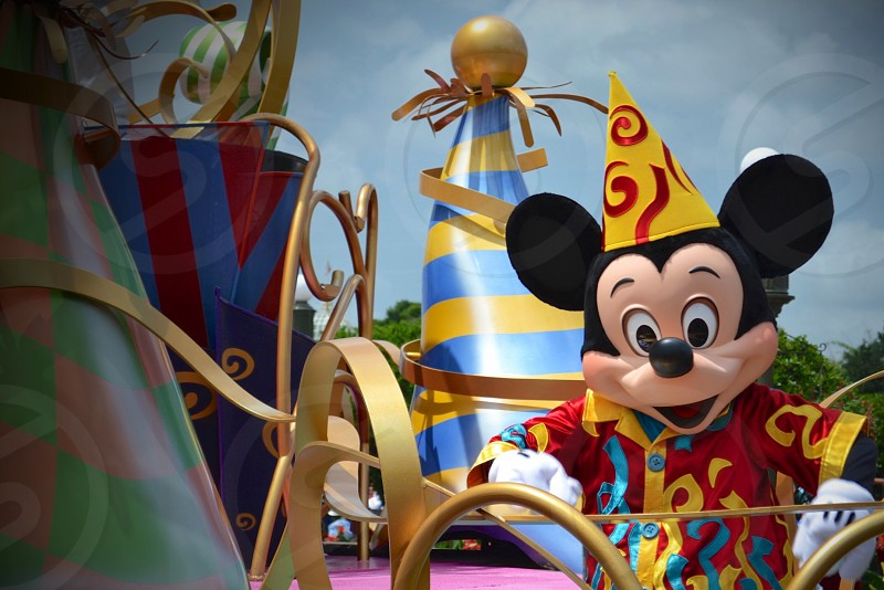 Mickey Mouse mascot wearing red-and-yellow shirt and cone-shaped hat photo