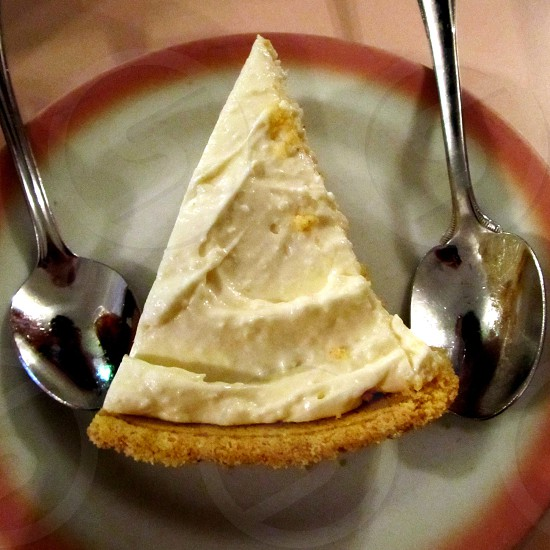 Lemon icebox pie with two spoons on white pink-rimmed plate on pink tablecloth photo