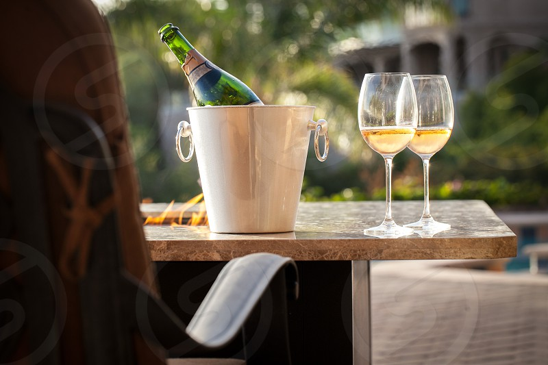 Two glasses of wine rest on the marble surface of an outdoor firepit next to a wine bottle in a silver bucket. photo
