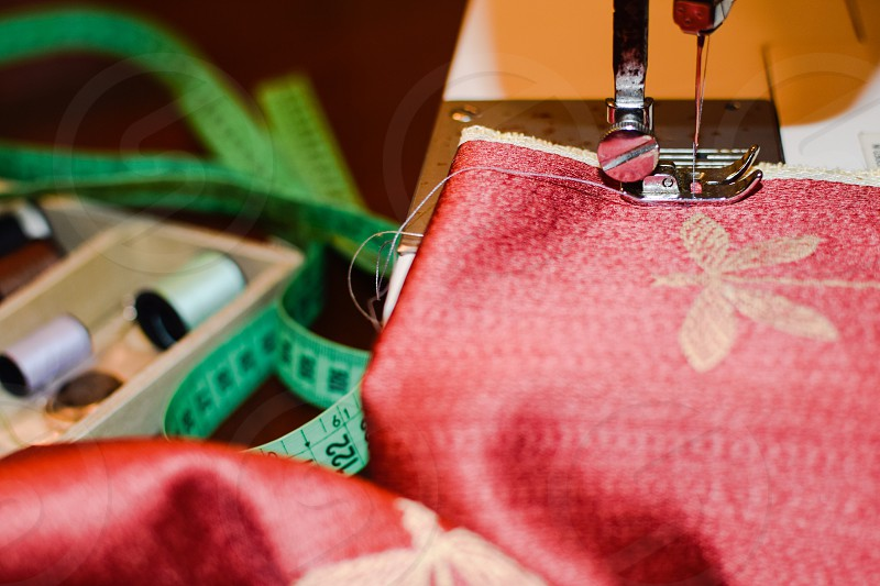 red and gray fabric on a sewing machine near a green measuring tape photo