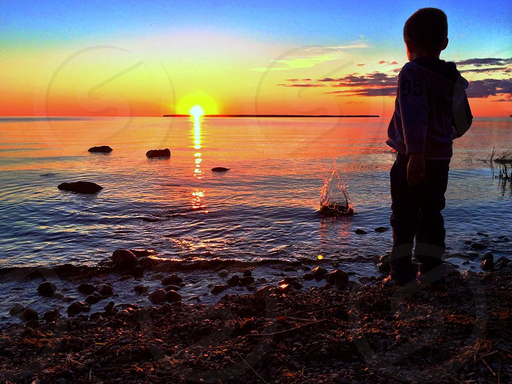 Silhouette of boy throwing rocks in Lake Michigan on sunset beach in door county. photo