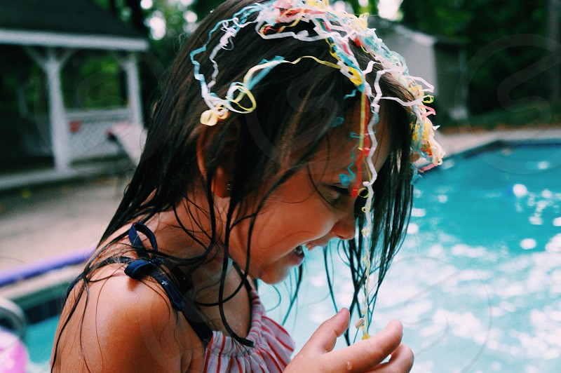 girl in pool with colored strings on her head photo