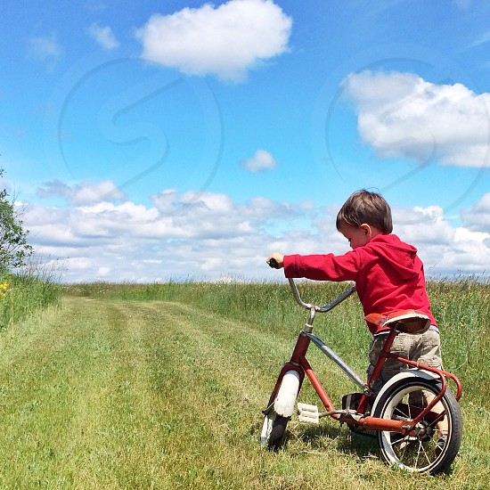 boy in red hoodie sweatshirt walking a red black tricycle through green grassy field photo