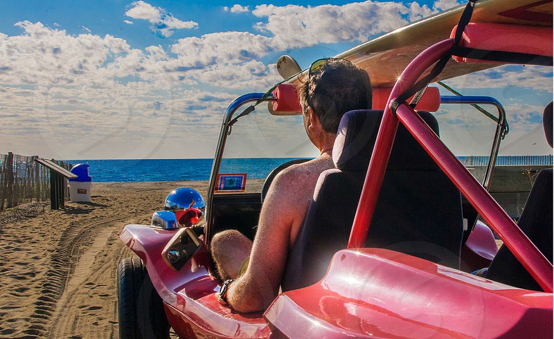 man driving a pink dune buggy on the beach photo