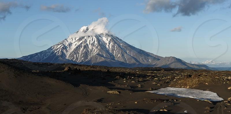 Panorama: beautiful mountain landscape at sunset - view of cone of Bolshaya Udina Volcano. Russia Far East Kamchatka Peninsula Klyuchevskaya Group of Volcanoes. photo
