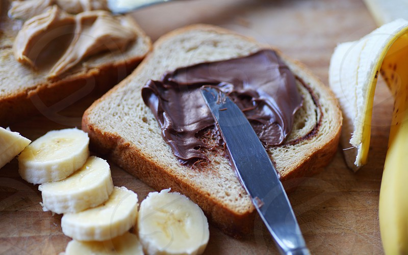 Making a sandwich of chocolate spread peanut butter and a banana photo