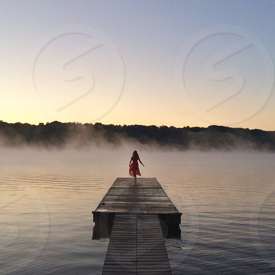 woman standing on wooden dock over the water with white mist above the water at distance photo