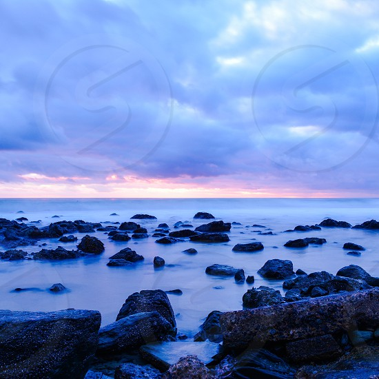 black rocks by calm sea under cloudy sky photo