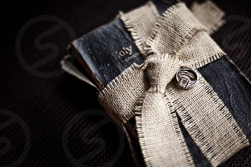 holy bible wrapped with brown ribbon with silver diamond ring on top photo