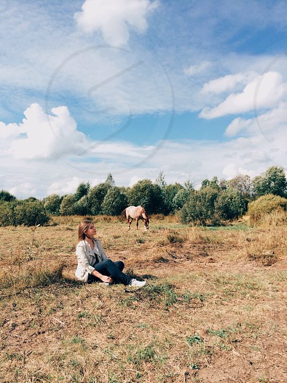 woman sitting on brown and green grassy field with brown horse on background by green trees under blue sky with white clouds during daytime photo