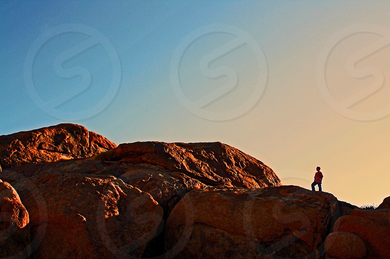 Silhouetted boy stands on top of rocky mountain at sunset in Joshua Tree Nation Park California photo
