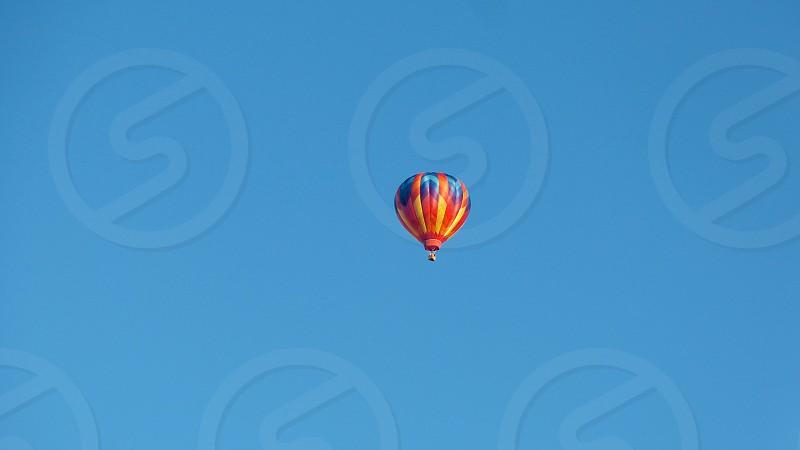 Multi-color hot air balloon against blue sky photo