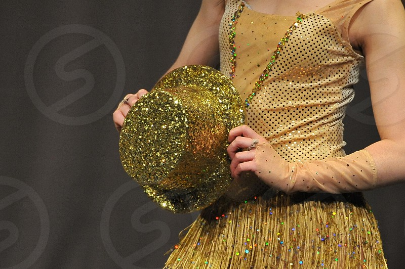 Dancer holding a gold hat. photo