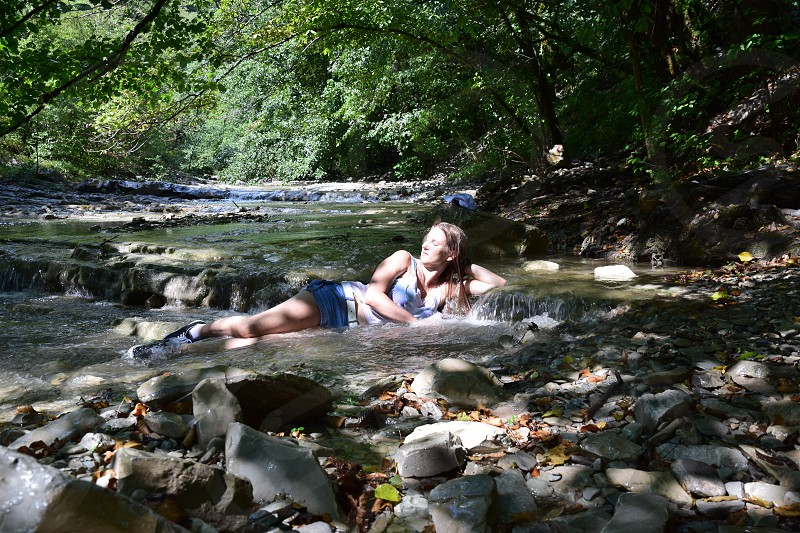 woman in white tanktop and blue denim shorts outfit lying on the river bed with rushing water surrounded by green trees during daytime photo