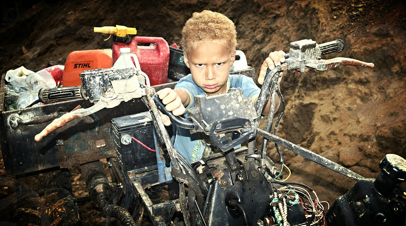 Grumpy Boy on Junk-Filled ATV photo
