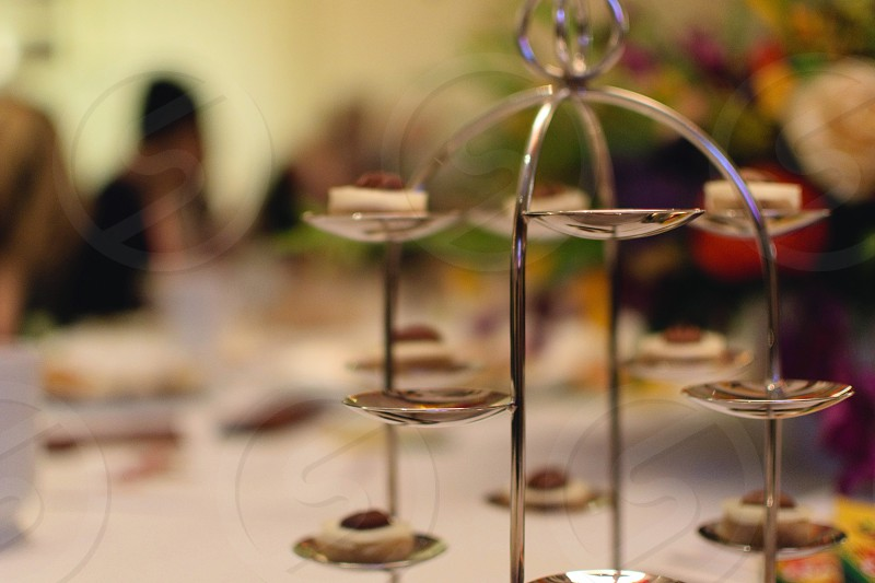 selective focus photography of stainless multi-layered steel confectioneries stand in the middle of gathered people photo