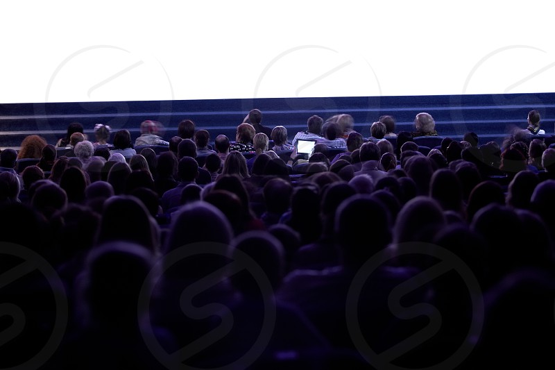 Wide shot of sihouettes of people from back watching cinema. Somebody filming the movie using tablet. Empty cinema screen photo
