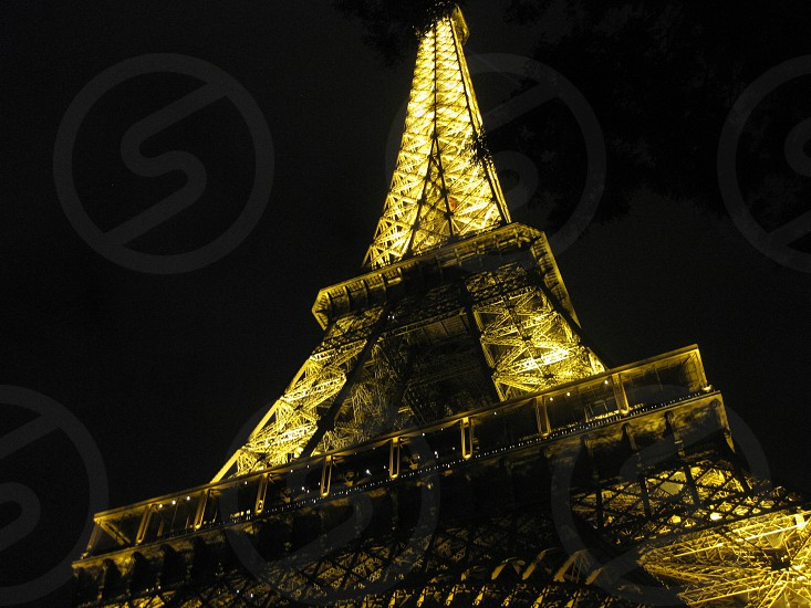 Eiffel Tower lit up at night in Paris France. photo