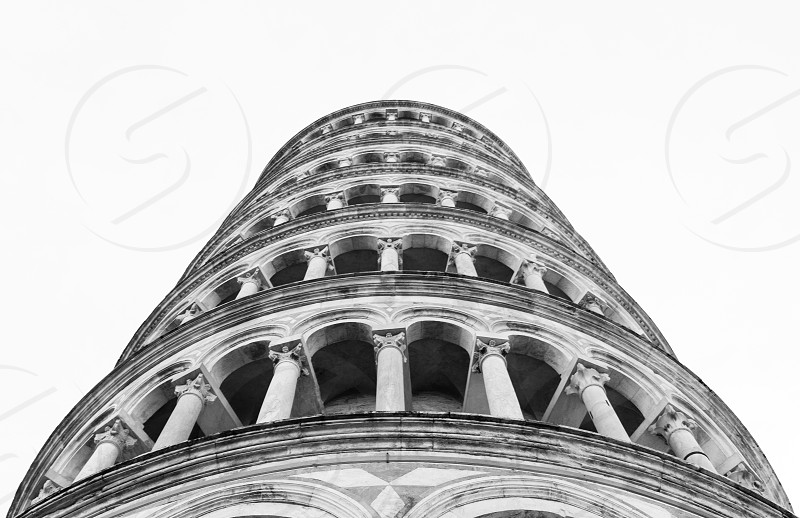 Black and white photos of the famous tower of Pisa in the celebrated Piazza del Duomo in Tuscany photo