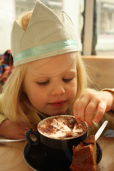 Child happily dips food into hot chocolate photo